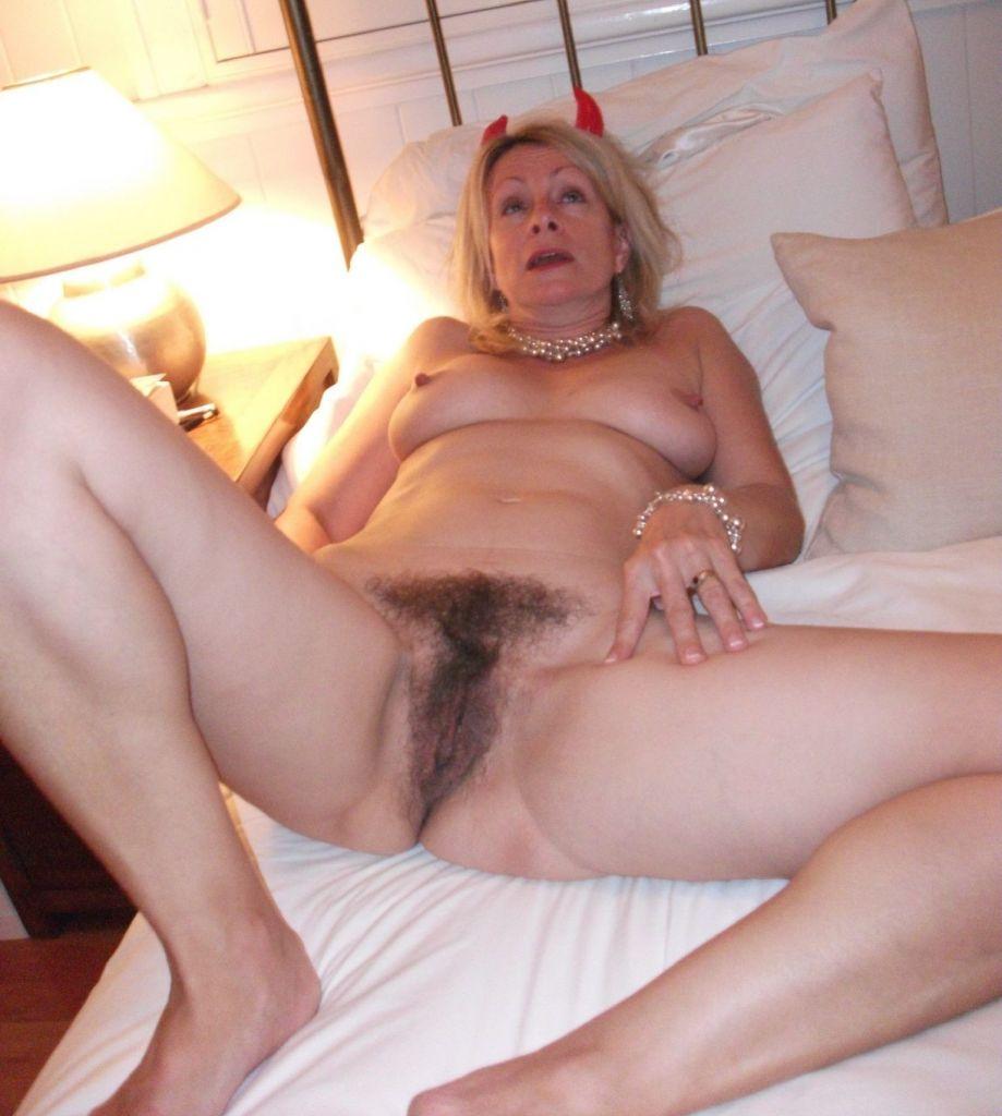 Мадам с рожками лежит на кровати с лохматой писькой