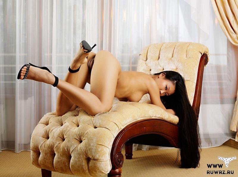 Азиатка умостилась на кресле