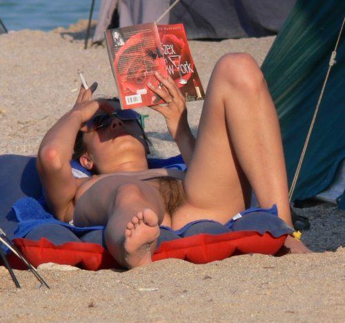 Не бритая пизда курит и читает на пляже