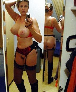 Грудастая зрелка позирует перед зеркалом